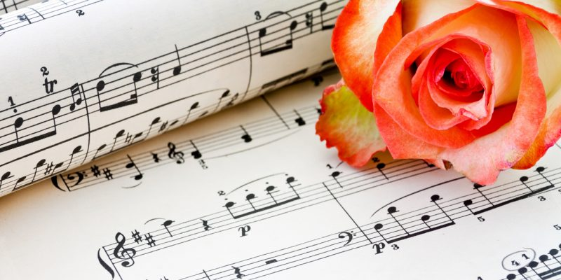 Old sheet music with rose alf background